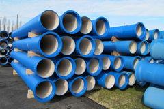 Concrete pipes for transporting water and sewerage. Piles of concrete pipes for transporting water and sewerage Royalty Free Stock Images