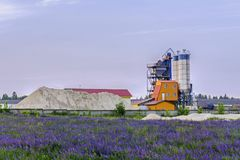 Concrete plant among flowering fields. Concrete batching plant among flowering fields in the countryside royalty free stock photos
