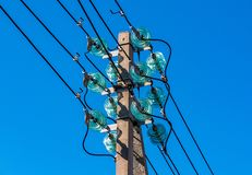 Concrete pole with electrical wires and high-voltage distribution insulators as part of a transmission line. Against a blue sky royalty free stock images