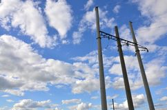 Concrete pole with wires of power line against the background of blue cloudy sk. Y Royalty Free Stock Photography