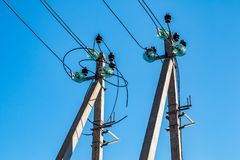 Concrete poles with electrical wires and high-voltage distribution insulators as part of a transmission line. Against a blue sky royalty free stock photos