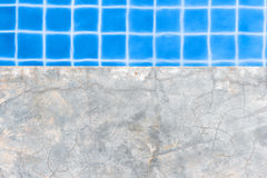 Concrete pool edge with swimming pool as background. Stock Photography