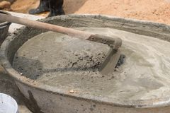 Concrete mix. Concrete pouring during commercial concreting floors of building Worker with gum boots spreading ready mix concrete Stock Photos