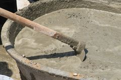 Concrete mix. Concrete pouring during commercial concreting floors of building Worker with gum boots spreading ready mix concrete Royalty Free Stock Photo