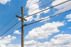 Concrete power pole and electrical wires in thailand with beautiful cloudy blue sky at afternoon sunlight and shadow Royalty Free Stock Photo