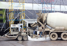 Concrete pump and  mixer to work together  pouring cement floors in the shopping center for repair. Concrete pump and concrete mixer to work together to pouring Stock Photography