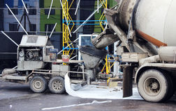 Concrete pump and  mixer to work together  pouring cement floors in the shopping center for repair. Concrete pump and concrete mixer to work together to pouring Royalty Free Stock Photos