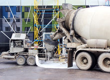 Concrete pump and  mixer to work together  pouring cement floors in the shopping center for repair. Concrete pump and concrete mixer to work together to pouring Royalty Free Stock Photography