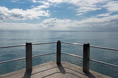 Concrete Railing Against Ocean and Blue Cloudy Sky Royalty Free Stock Image