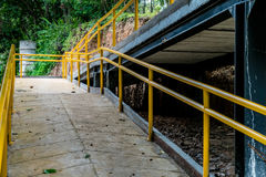 Ramp for wheelchair. Concrete ramp for wheelchair with yellow iron railing in the park Royalty Free Stock Photos