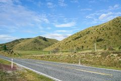 Concrete road along green hill in Lindis Pass New Zealand with clear blue sky. Concrete road along green hill in Lindis Pass New Zealand with bright blue sky Royalty Free Stock Photography