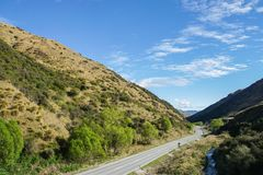 Concrete road along green hills in New Zealand for trip. Concrete road along green hills in New Zealand for road trip Stock Image