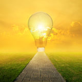 Concrete road and Big idea bulb in Grass fields and Sunset Royalty Free Stock Photo