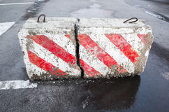 Concrete road block with warning pattern. Concrete road block with warning red and white diagonal striped pattern stock image