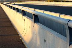 Concrete road bridge barrier with metal guard rails. Concrete road bridge barrier with strong metal safety guard rails mounted on top at sunset royalty free stock image
