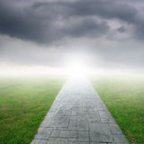 Concrete road in Grass fields and rainclouds Royalty Free Stock Photos