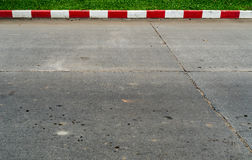 Concrete road with red and white. Curb and green grass sidewalk Stock Photos