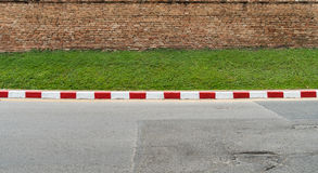 Concrete road with red and white. Curb and old brick wall Stock Images