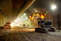Concrete Road Tunnel Construction Excavator. And Articulated Dump Truck Stock Images