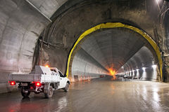 Concrete Road Tunnel Under Construction. A concrete road tunnel under construction with a white utility vehicle in the foreground Royalty Free Stock Photography