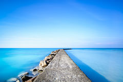 Concrete and rocks pier or jetty on blue ocean water. Concrete and rocks pier or jetty on a blue ocean water. Long Exposure photography Royalty Free Stock Images
