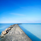 Concrete and rocks pier or jetty on blue ocean water Stock Photography