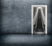 Concrete room with access to escalator through the doorway Royalty Free Stock Photo