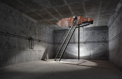 Concrete room under ground with a ladder to the surface from which the light comes. Technical room ventilation shaft Stock Photography