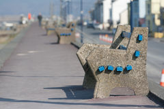 A concrete seat situated on a deserted promenade Royalty Free Stock Photos