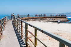 Concrete SeaWall with Metal Railing Overlooking La Jolla Children`s Pool Stock Photo