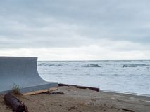 Concrete seawall protecting property from waves from an ominous storm in distance royalty free stock image