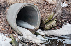 Concrete sewer culvert emptying in winter. Royalty Free Stock Photo