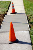 Concrete Sidewalk Repair on City Street with Cones. New poured slab patch repair of a concrete city sidewalk on a residential street with warning safety cones Royalty Free Stock Photos