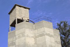 A concrete silo with a small structure made from blocks on its roof. Royalty Free Stock Photography