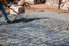 Concrete Slab spreading by Worker to achieve level. Wire mesh showing Stock Images