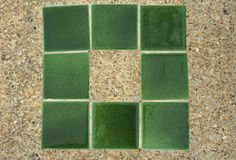 Concrete with small gravel texture with green tiles. Outdoor Stock Photography