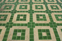 Concrete with small gravel texture with green tiles. Sand Royalty Free Stock Photography