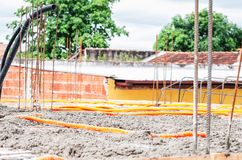 Concrete spread over the slab of a house under construction. Structural parts of a house, building background. Steel beams and electrical mains piping on the stock photo