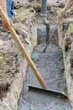 Concrete spreading. Construction workers spreading fresh concrete being poured into foundation excavation Stock Photo