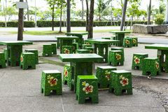 Concrete Square table set green color and floral print chairs in park.  stock image