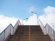 Concrete stair of footbridge with yellow line over blue sky. And white clouds background Stock Photo