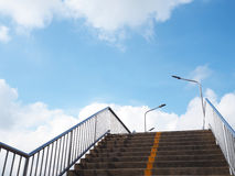 Concrete stair of footbridge with yellow line over blue sky. And white clouds background Royalty Free Stock Images
