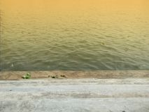 Sunbeam on river. Concrete stair pier on the dirty river with orange sunbeam Stock Photography