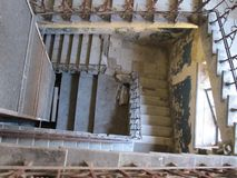 Concrete staircase with wrought iron railings inside an old abandoned house stock photo