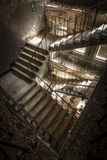 Concrete stairs in an abandoned building. Concrete stairs illuminated with a picturesque light in an abandoned building in a sunny day. The light enters through Stock Photography