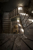 Concrete stairs in an abandoned building. Concrete stairs illuminated with a picturesque light in an abandoned building in a sunny day. The light enters through Stock Photo