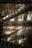 Concrete stairs in an abandoned building. Concrete stairs illuminated with a picturesque light in an abandoned building in a sunny day. The light enters through Stock Image
