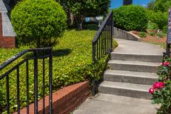 Concrete stairs and curving walkway bordered by brick retaining wall and groundcover. Horizontal aspect stock photos