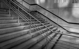 Concrete stairs and handrails shadows in modern district. Black and white photography of new concrete stairs and handrails focused and wall in background during Stock Images