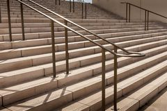 Concrete stairs and handrails shadows in modern district. New concrete stairs and handrails focused and wall in background during the afternoon Stock Photo